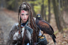 Beautiful Viking Warrior Woman In Woods Wearing Fur Collar, Braided Hair And Specific Makeup With Face Covered In Blood Holding Hawk In Hand. Northern Woman With Her Predator In Forest