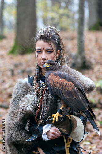 Outdoor portrait of Viking warrior woman in woods wearing fur collar, with braided hair and specific makeup with face covered in blood holding hawk in hand Canvas Print