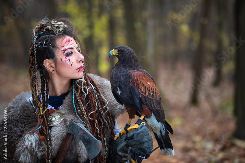 Outdoor portrait of Viking warrior woman princess in woods wearing fur collar, braided hair and specific makeup with face covered in blood holding hawk in hand Wallpaper Mural