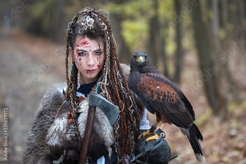 Beautiful Viking warrior woman in woods wearing fur collar, braided hair and specific makeup with face covered in blood holding hawk in hand Canvas Print