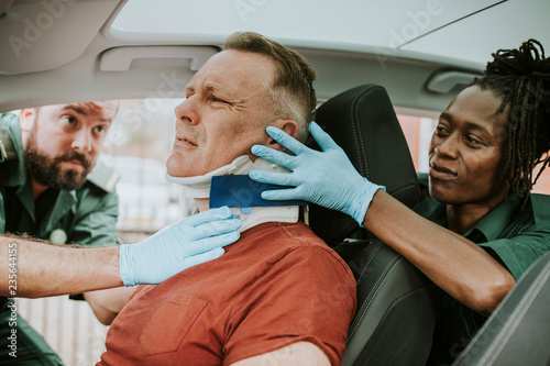 Paramedic placing a cervical collar to an injured man from car accident Canvas Print