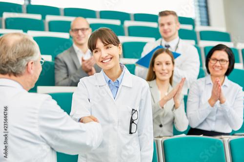 Leinwand Poster Handschlag zwischen junger Ärztin und Dozent