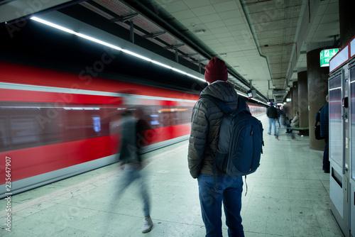 Fotografie, Obraz  Mann mit Rucksack wartet auf den Zug am Bahnhof