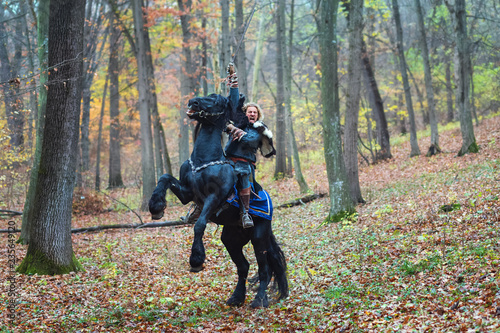 Photo  Viking warrior man riding horse in forest holding sword attacking