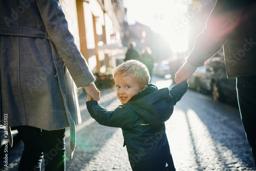 Fotografia, Obraz  A rear view of small toddler boy with unrecognizable parents walking outdoors in city