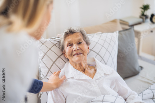 Obraz A health visitor talking to a sick senior woman lying in bed at home. - fototapety do salonu