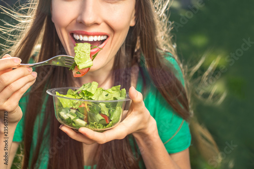 Fotografía Beautiful caucasian woman eating salad over green natural background