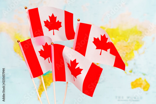 Small Map Of Canada.The Four Small Flags Of The Canada Waving In The Wind Against The