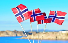 Four Flags Of Norway Are Fluttering In The Wind Against The Blue Sky And Sea Background. Concept Of Norwegian Constitution Day.  Celebrated On May 17.