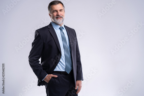 Fototapeta Happy satisfied mature businessman looking at camera isolated on white background. obraz