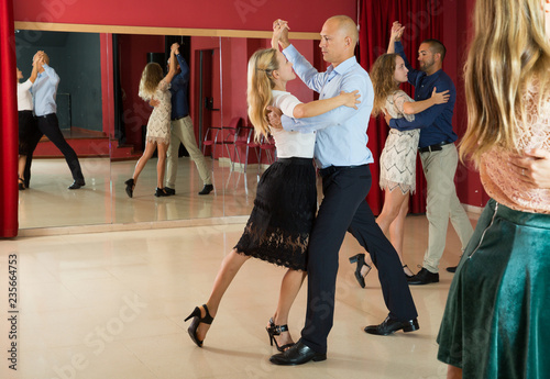 Positive adult couples dancing tango together  in modern studio - 235664753