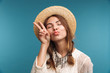 Cute pretty woman showing peace gesture isolated over blue wall background.