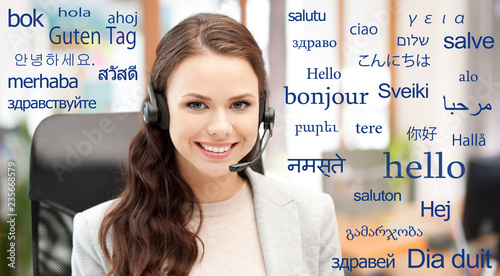 translation, communication and technology concept - smiling female helpline operator with headset at office over greeting words in different foreign languages