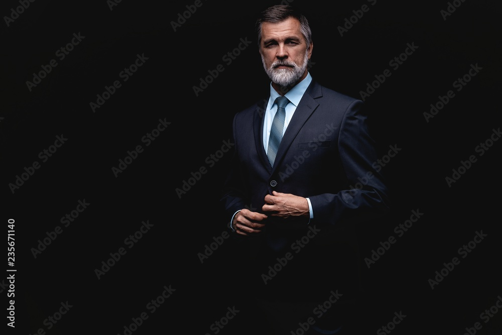 Fototapeta Handsome mature business man isolated on black background