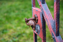 Wrought Iron Handle At An Open Old Garden Gate With Worn Red Color, Copy Space, Close Up