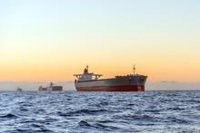 Huge Ships At Sea At Sunset With Orange Sky Bacjground