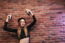 Image Of Aggressive Hip Hop Girl 20s, Standing Against Brick Wall With Spray Cans