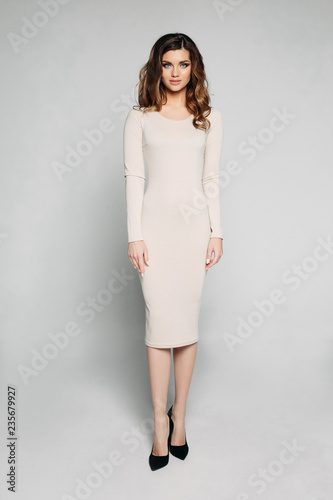 9fe7c40cbc Full length studio shot of brunette woman wearing casual mid-length ivory  dress and black high heels looking away posing over grey background. ...  See More