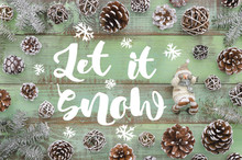 Let It Snow And Snowman On Green Wooden Plank Background With Pine Cones And Fit Tree, Winter New Year Greeting Card, Banner, Top View