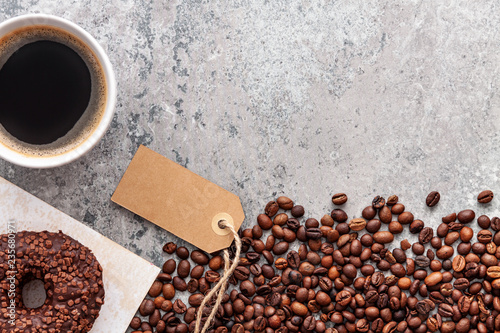 Fotografie, Obraz  Donut decorated with dark chocolate balls, roasted coffee beans and cup of coffee on dark gray stone background, top view, copy space