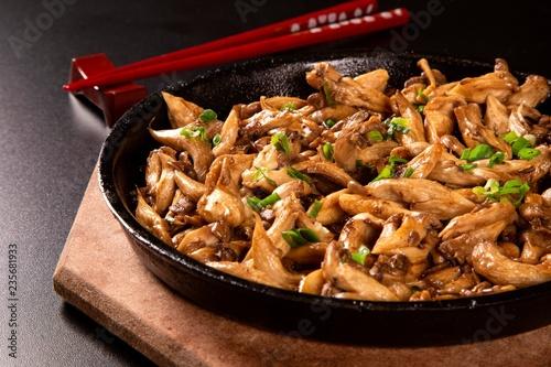 Valokuva  shimeji mushrooms in iron pan in a black background.