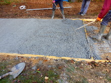 Workers Levelling Off Freshly Poured Cement In The Construction Of A Concrete Driveway