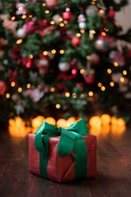 The Gift Lies On A Dark Wooden Floor Under The Christmas Tree With A Glowing Gerland.