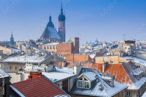 Fototapeta Krakow in Christmas time, aerial view on snowy roofs in central part of city. St. Mary's Basilica on Main Square. Poland. Europe. obraz