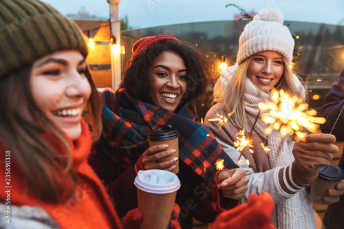 Photo Young friends talking with each other drinking coffee outdoors winter concept holding bengal lights