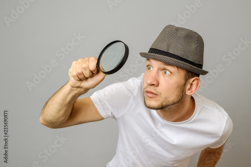 Astonished man looking through a magnifying glass Canvas Print