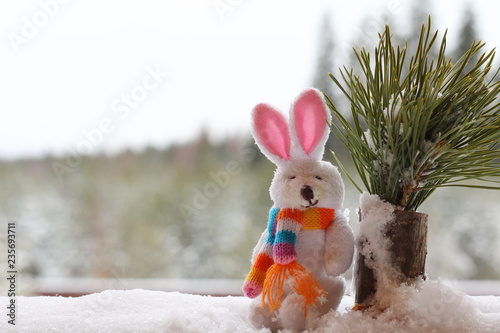 Fotografie, Obraz  A white rabbit figurine in a snowdrift against the backdrop of a winter forest
