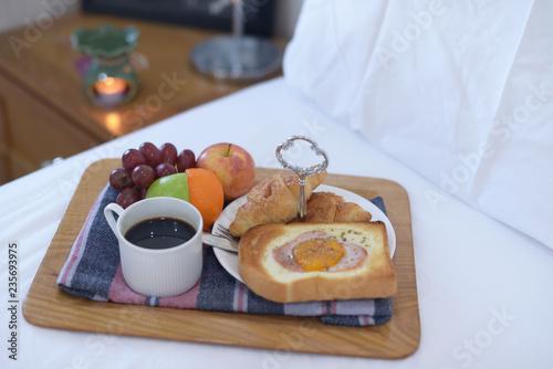 Breakfast on bed with coffee, croissants Window light