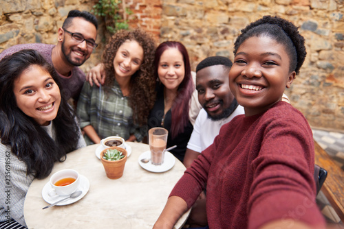 Diverse young friends taking selfies together in a cafe courtyard Fotobehang