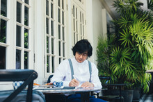 Elegant Asian Businessman Sitting At Cafe Terrace And Writing In His Notebook.