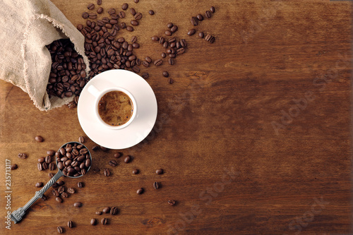 Foto op Plexiglas Cafe Coffee cup and coffee beans on wooden background. Top view.