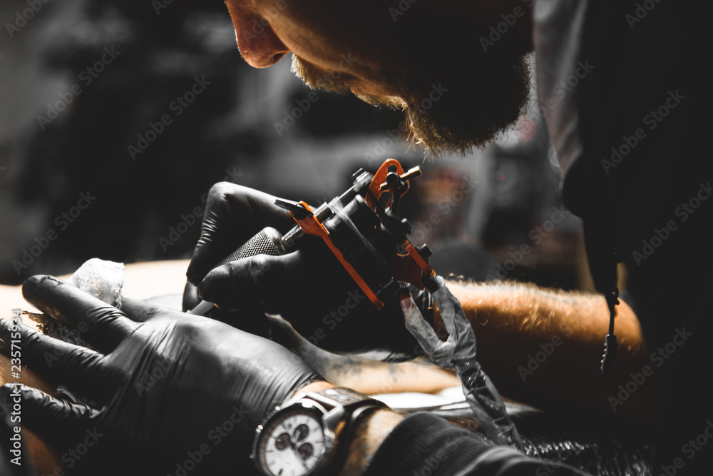 Fototapeta The tattoo artist creates a picture on the body of a man. close-up of tattoo machines and hands