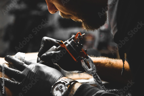 Fotografiet The tattoo artist creates a picture on the body of a man