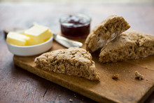 Close Up Of Whole Wheat Apple And Pecan Scones On Wooden Cutting Board