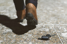 Car Keys Dropped From A Woman Pocket On The Night Footpath And Her Silhouette Is Walking Away.