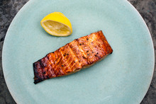 Close Up Of Grilled Salmon With Lemon Slice Served On Plate
