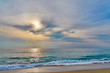 Sunset at the tropical beach, sun behind clouds reflects on water and waves with foam hitting sand.