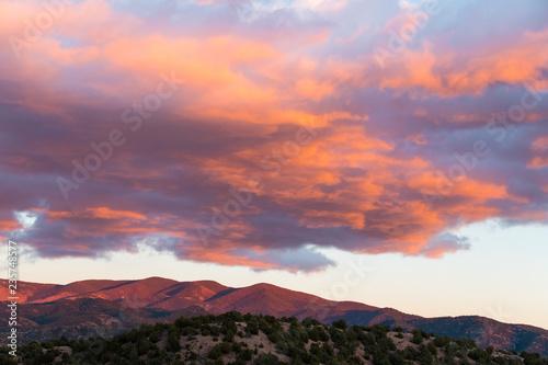 Naklejka premium Dramatyczny, piękny zachód słońca rzuca fioletowe i pomarańczowe kolory na chmury i góry Sangre de Cristo w pobliżu Santa Fe w Nowym Meksyku