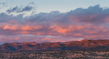 Dramatic, Beautiful Sunset Casts Purple And Orange Colors And Hues On Clouds And Mountains Over A Neighborhood In Tesuque, Near Santa Fe, New Mexico
