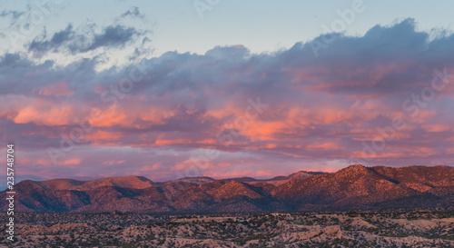 Fototapeta premium Dramatyczny, piękny zachód słońca rzuca fioletowe i pomarańczowe kolory i odcienie na chmury i góry nad okolicą w Tesuque, niedaleko Santa Fe w Nowym Meksyku