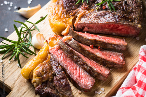 Grilled beef steak ribeye on wooden cutting board.