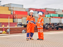 Dock Workers Talking By Railroad Tracks