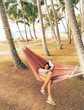 Woman lying on hammock between palm trees