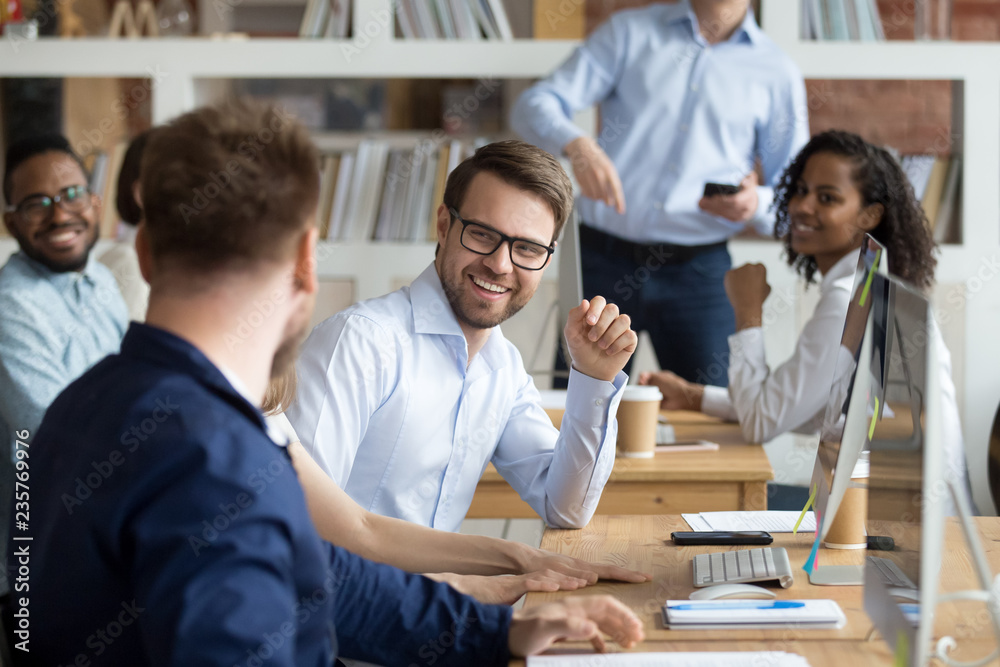 Fototapety, obrazy: Multiracial work team having fun and laughing together, employees working and discussing about funny news in shared workspace, teamwork, good relationships in team, friendship concept