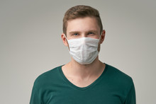 A Young Man With A Protective Medical Mask With A Serious Expression Looking At The Camera. The Concept Of Protection Against Infectious Diseases.
