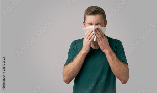 Canvas Print A man in a green t-shirt sneezes a napkin